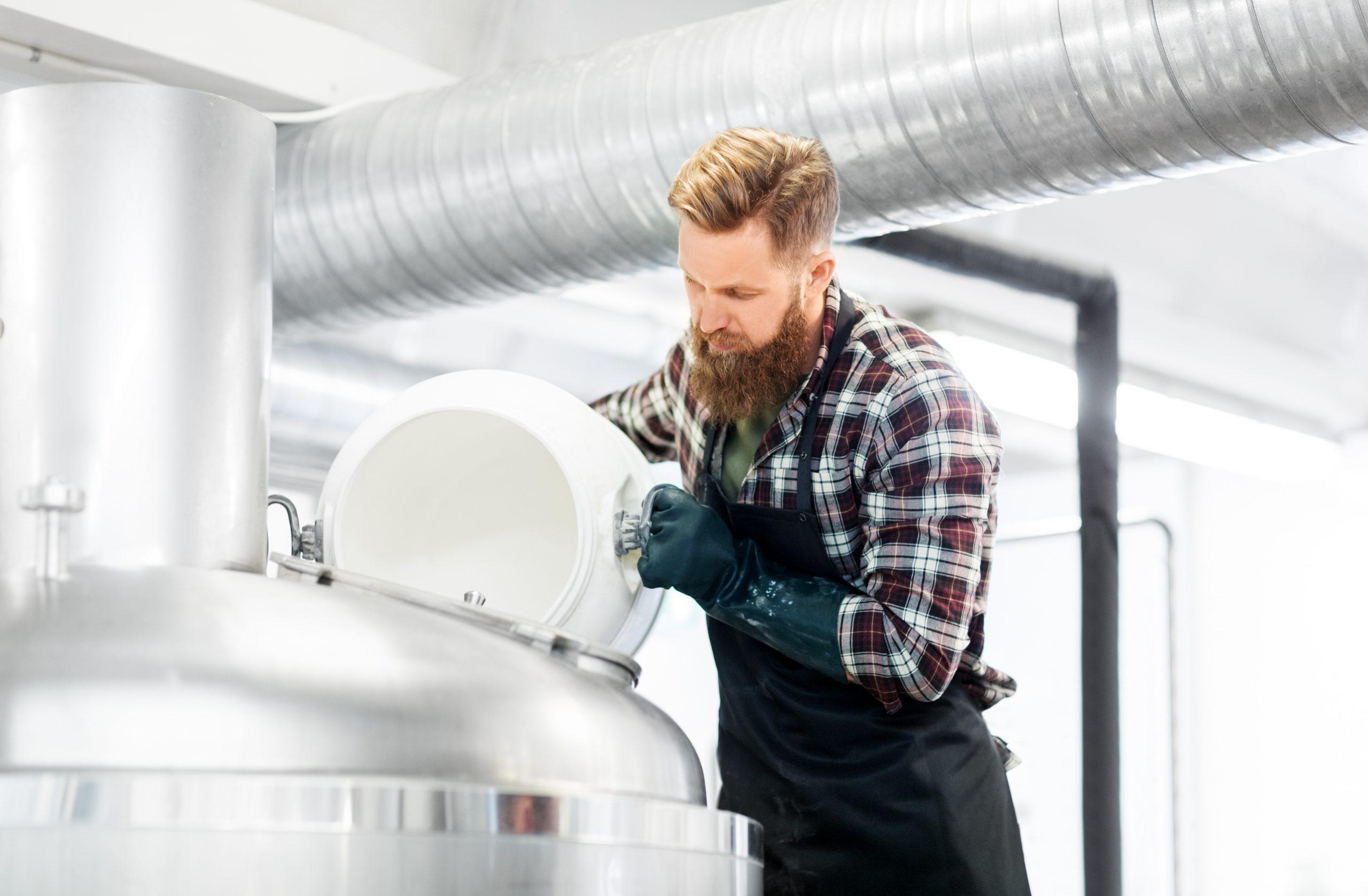 Man ledigt wit plastieken vat in een groot vat om bier te brouwen