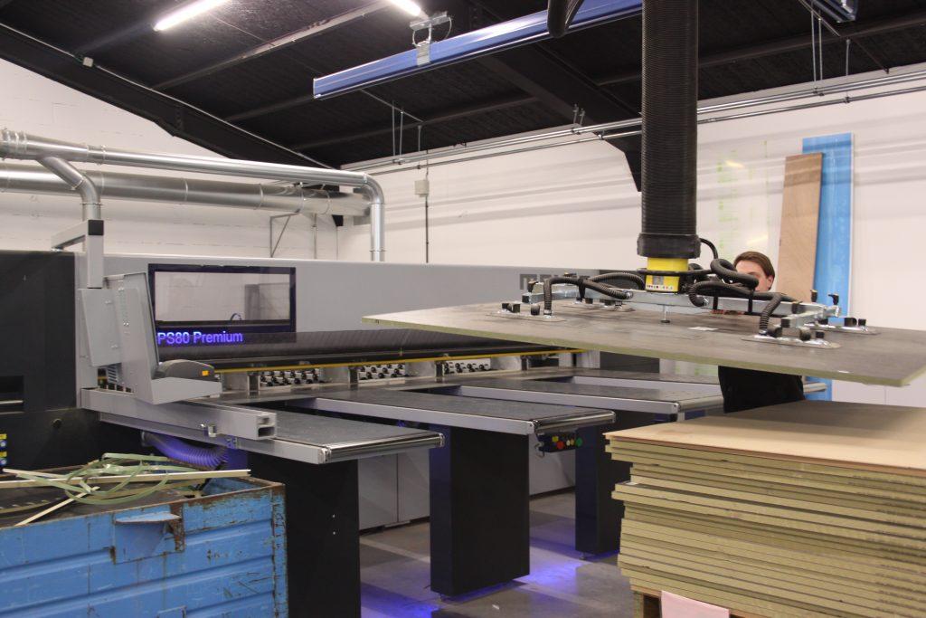 Werknemer Integral gebruikt vacuümhefsysteem met spider zuigvoet om houten plaat op CNC-machine te plaatsen.